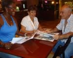 Fátima Navarro (i), Martha Baquero y profesor Denis Dau durante la planificación de los barriales de atletismo y ajedrez.