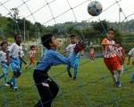 El portero Kenny Alarcón (c), de Cristo te Ama, intenta controlar el balón ante el disparo de Allan Flor (14), de Alfaro Moreno T.