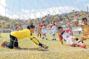 JOSÉ ALVARADO Jostín Marcatoma, de EF Joma (blanco y rojo), en el preciso instante de marcar el gol que dio el triunfo al equipo cuencano ante EF 3F Morales en la serie sub-9.