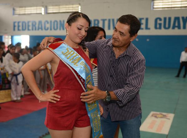 El director del torneo barrial de taekwondo, Fausto Quimba, ciñe la cinta como madrina del barrial a Joselyn Averos Suárez