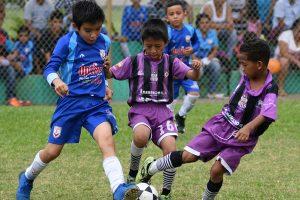 Jeison Berrezueta (i), del equipo que lleva el nombre del DT, Édgar Bueno, es marcado por Fabiano Sánchez y Dereck Vivas (d), de Escuela de Fútbol Santos Ecuador en la categoría sub-8 del barrial.